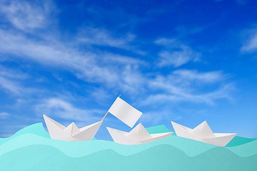 Three blank origami paper boat floating on the blue paper wave against blue sky
