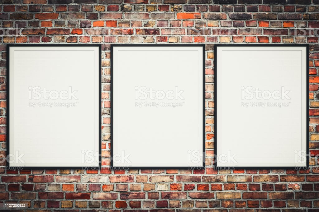 three blank picture frames on brick wall - framed poster mock-up with...