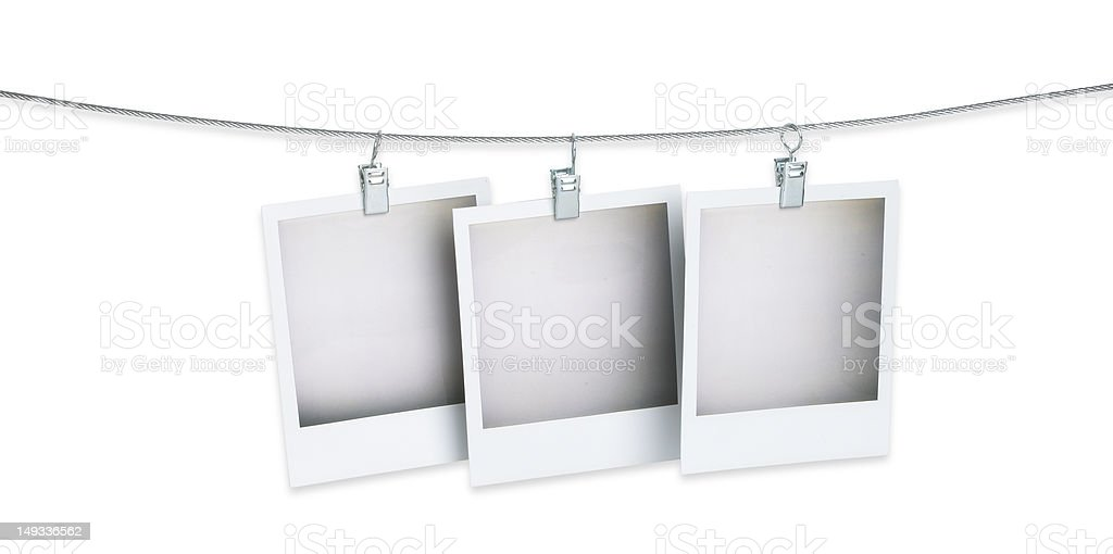 three blank polaroid pictures hanging on a wire with path stock photo
