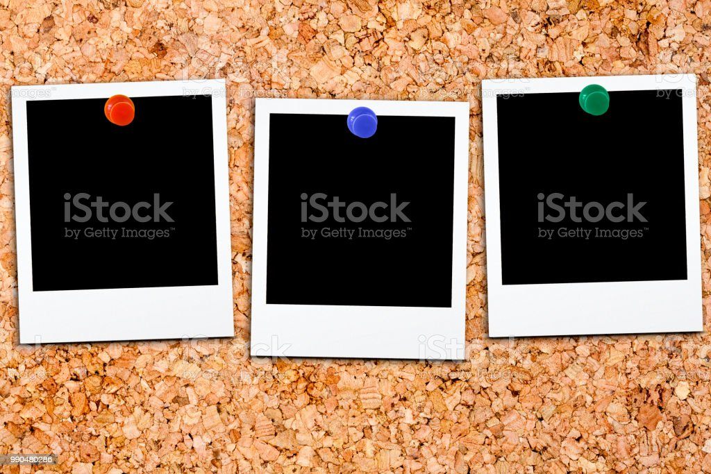Three blank polaroids affixed on cork board with colorful small thumb tack stock photo