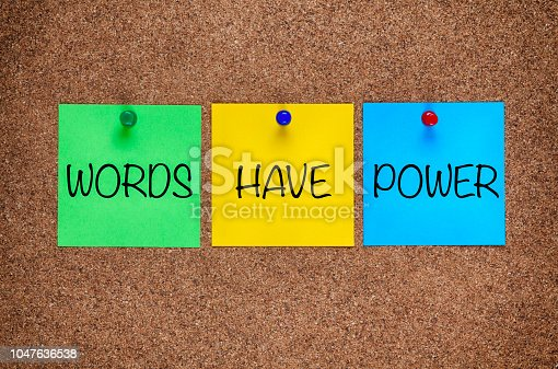 Three blanks post-it notes with phrase Words Have Power on corkboard.