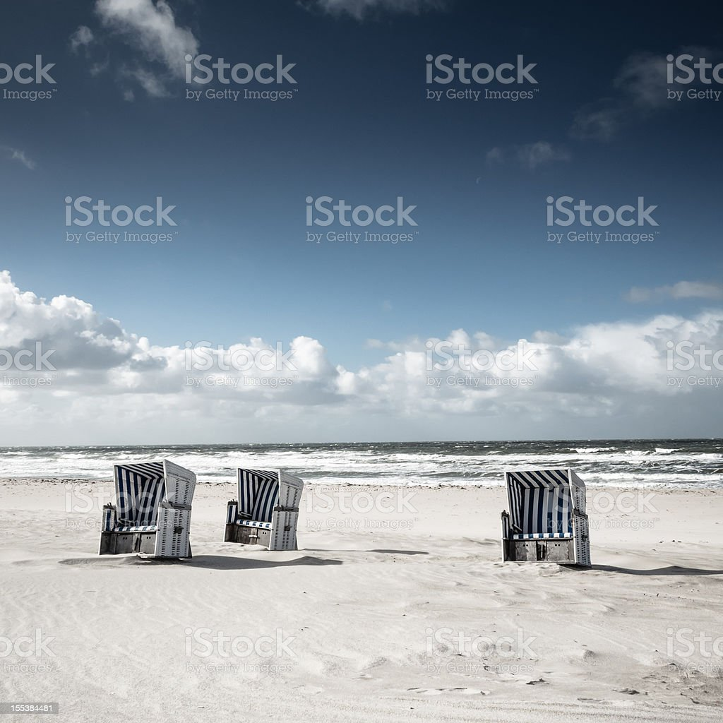 Three blue and white beach cabanas in sand on a sunny day stock photo