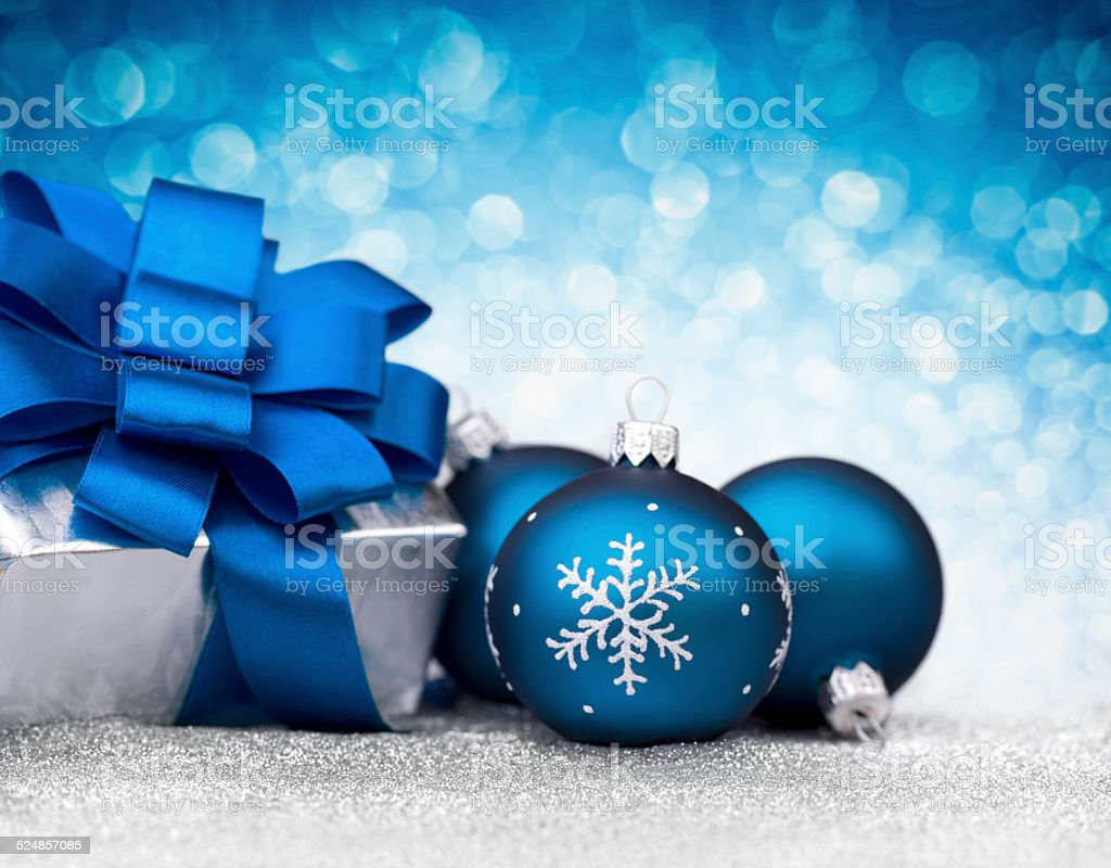 Three blue bauble and silver christmas gift on glitter stock photo