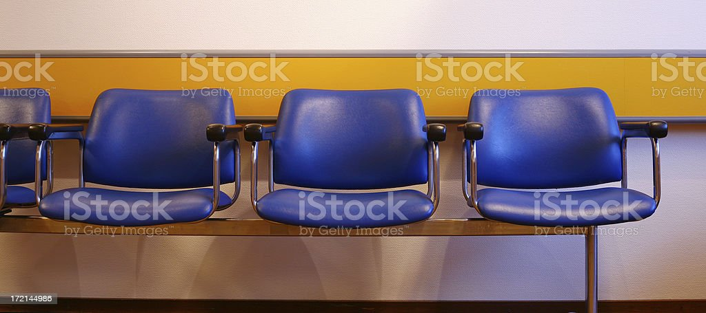 Three blue chairs against wall in waiting room, front view royalty-free stock photo