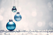 Three blue Christmas baubles with white background