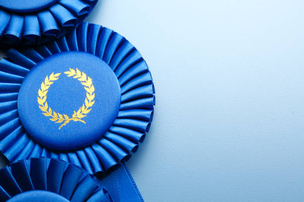 three blue ribbons on light- blue background - award ribbon stock photos and pictures