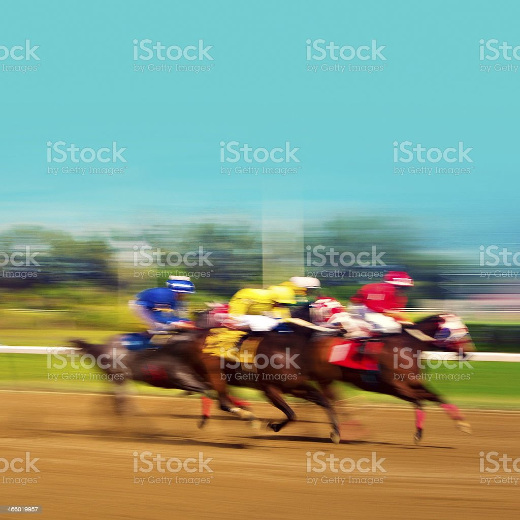 Three blurred racehorses on a dirt track stock photo
