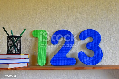 istock Three books, pencils in case and numbers one, two, three on shelf 1149997765