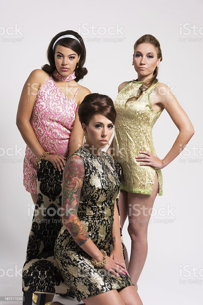 Three bored 60s styled women, one seated. royalty-free stock photo