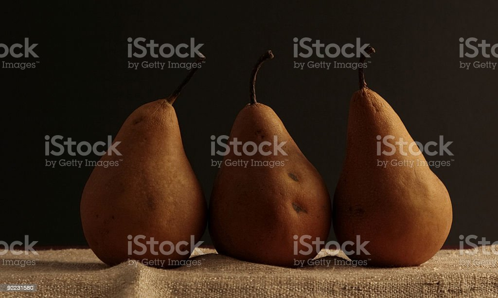 three Bosc pears in a row stock photo