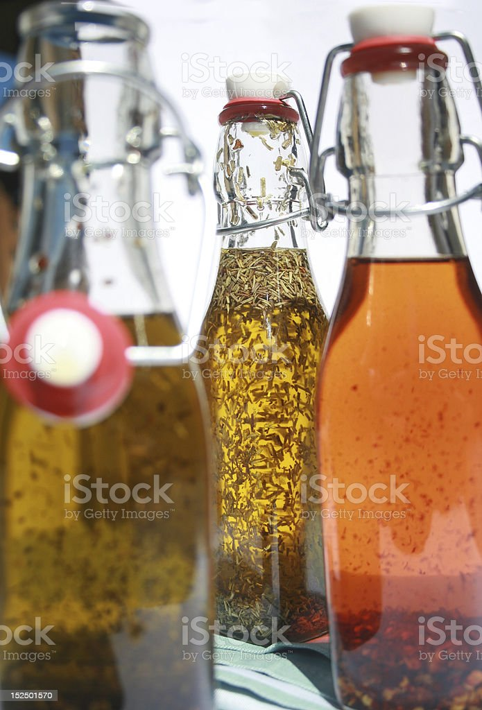 three bottles of dried herb and spice infused olive oil stock photo