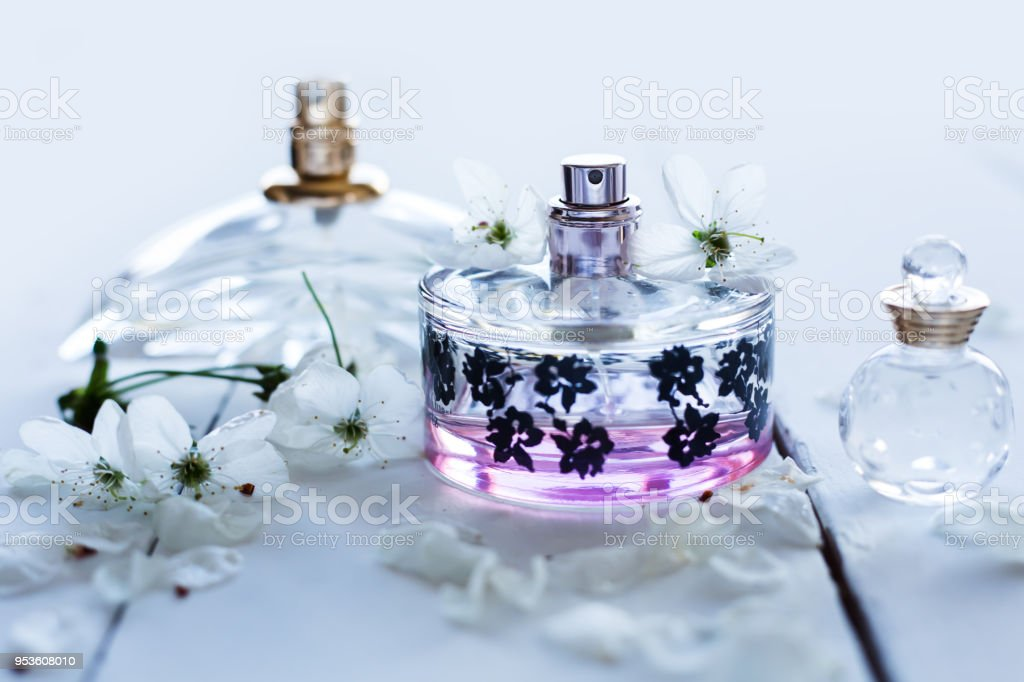 Three Bottles Of Perfume With White Flowers On Light Background
