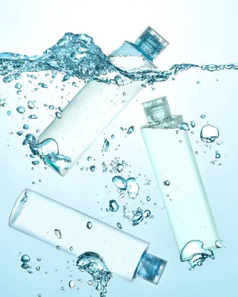 trois bouteilles d'eau thermale, cosmétique hydratante lotion sous l'eau. grosse vague sur la surface de l'eau et de nombreuses bulles de grands et petits dans l'eau. - démaquillant photos et images de collection