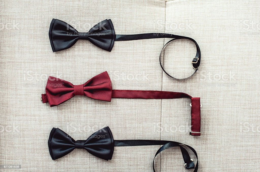 Three bow ties, two black and one red on a sofa. Team work, career,...