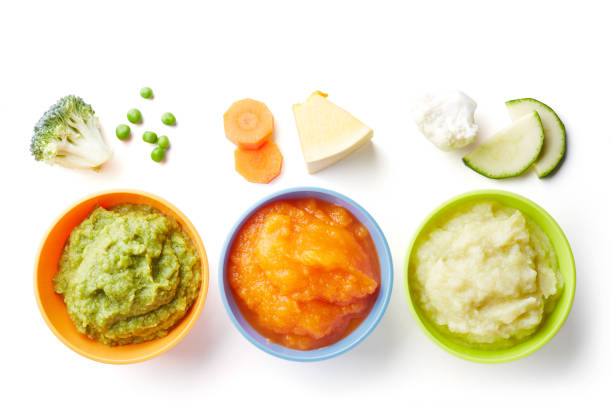 Three bowls of baby puree isolated on white from above stock photo