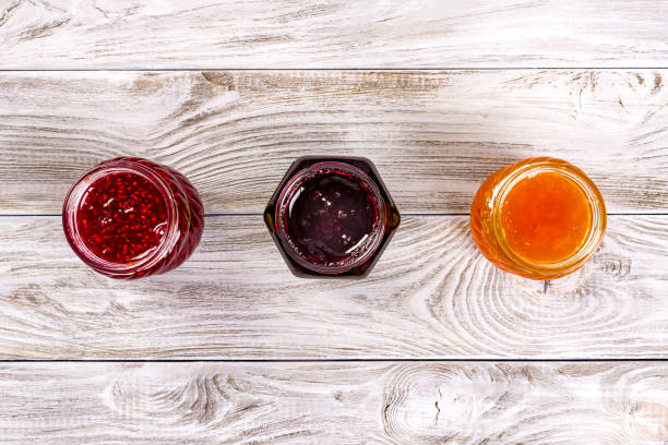 Three bowls with different jams on wooden table. Top view stock photo