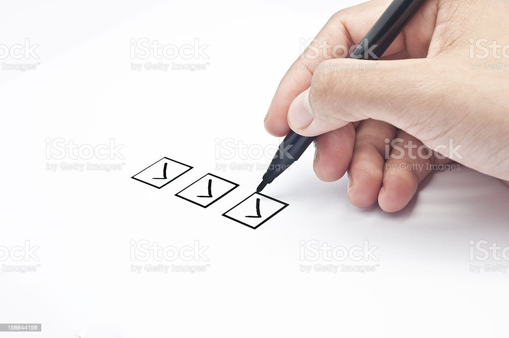 Three boxes with checkmarks done by pen on hand stock photo