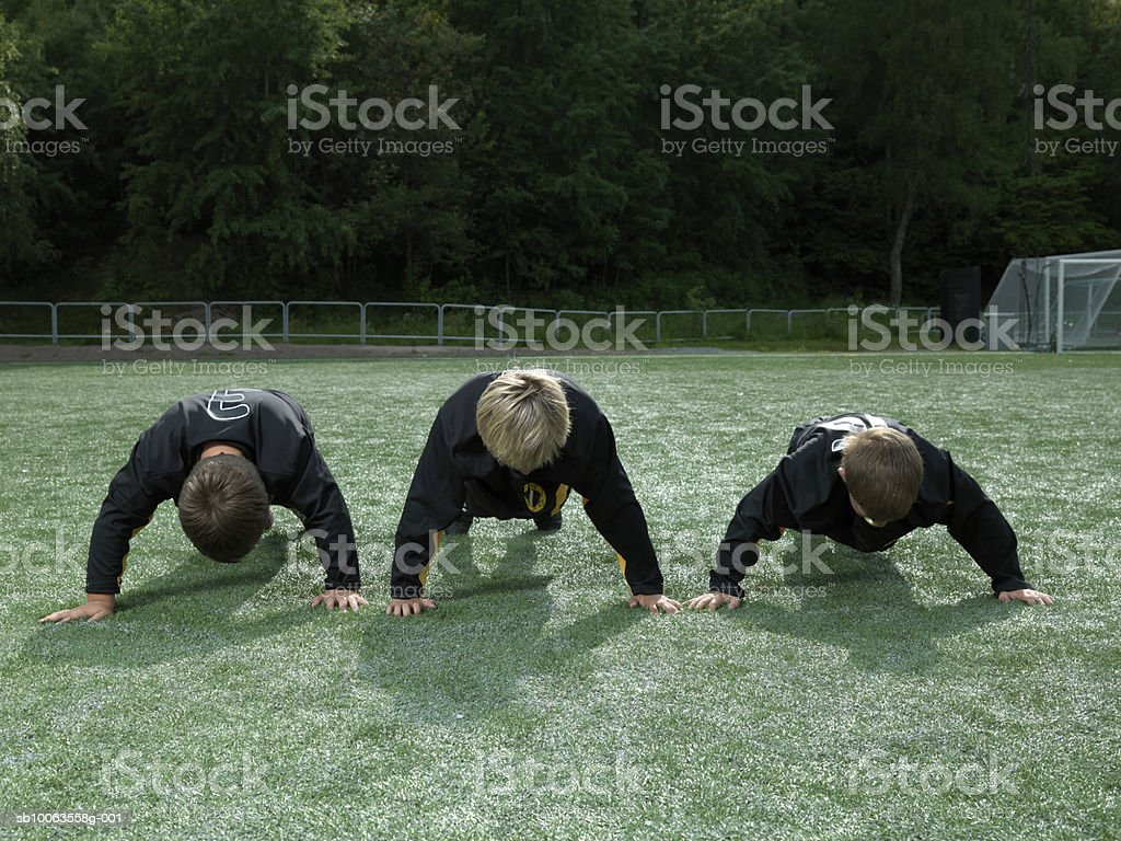 Three boys (9-10 years) doing push ups on soccer field photo libre de droits