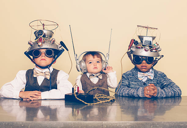 three boys dressed as nerds with mind reading helmets - genius stock photos and pictures