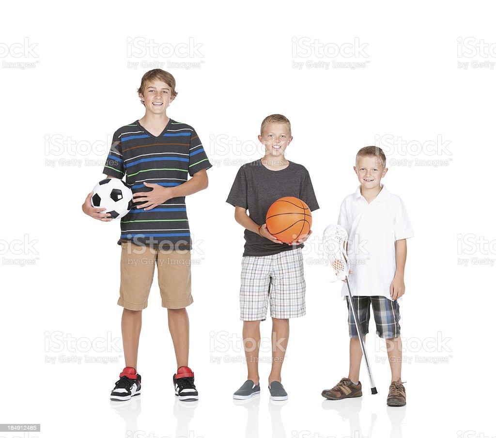 Three boys holding sports equipments stock photo