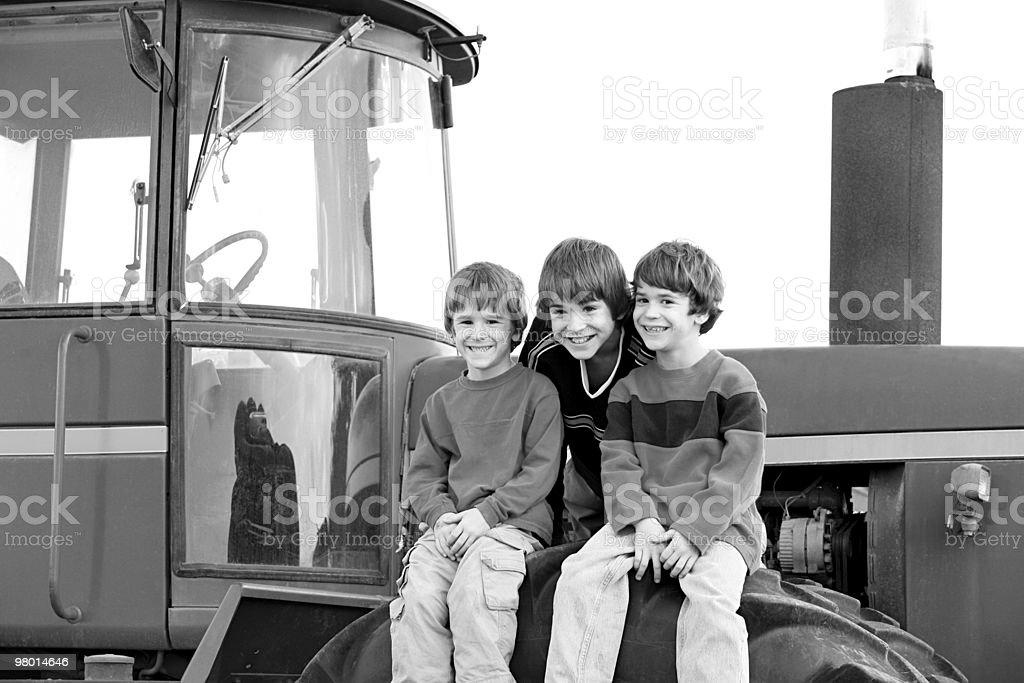 Tre ragazzi su un Trattore foto stock royalty-free