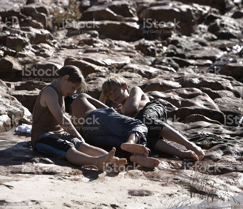 Three boys (10-13) resting on rock royalty free stockfoto