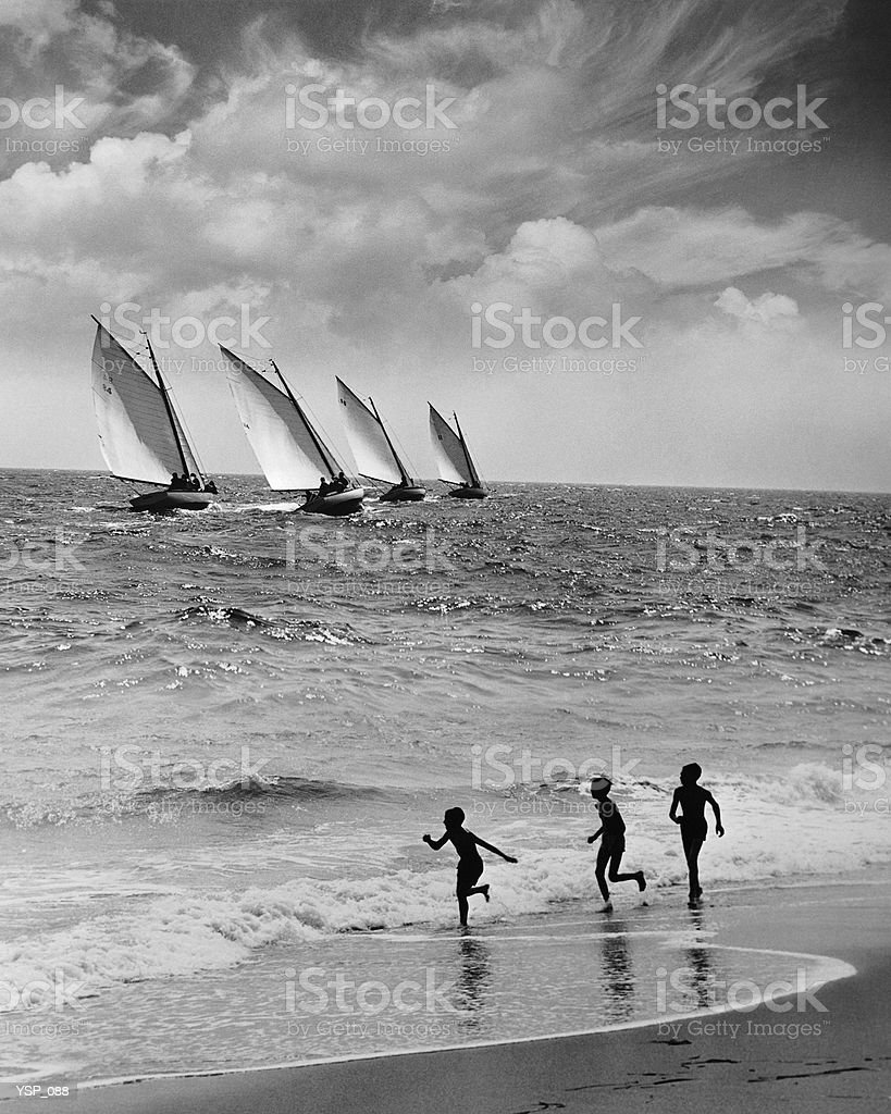 Three boys running along beach, following four sailboats out on ocean royalty-free stock photo