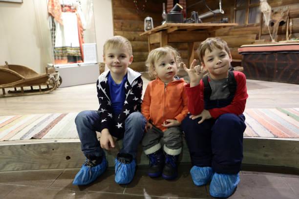 Tres niños sentados en el piso - foto de stock
