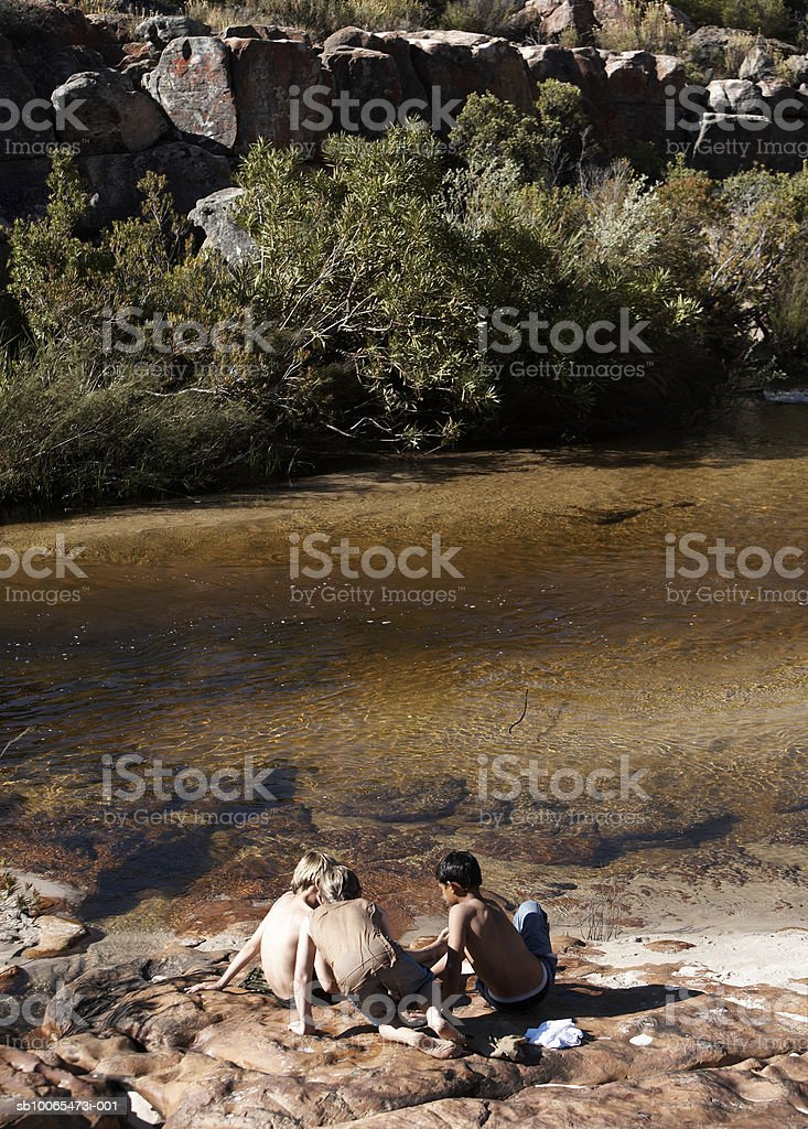 Three boys (10-13) sitting on rock by stream, elevated view 免版稅 stock photo