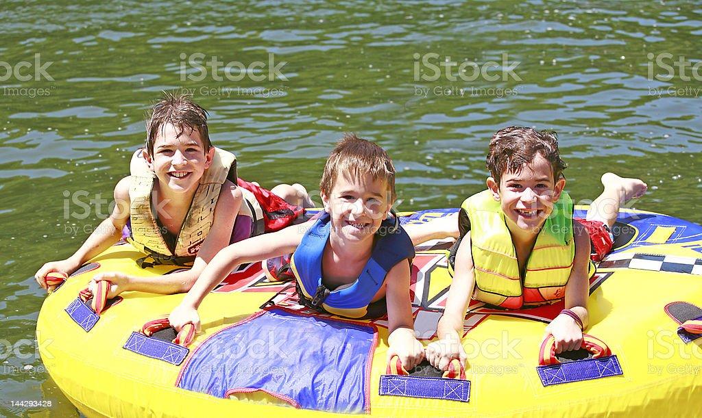 Three Boys Tubing royalty-free stock photo