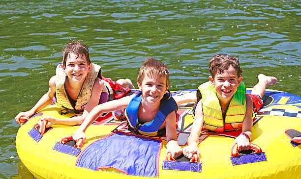 Three Boys Tubing stock photo