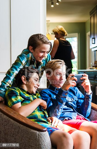 A mother is in the kitchen as three pre-teen boys use a smartphone in the living room.  She is out of focus but it is clear to see she is not monitoring what they are doing on-line.