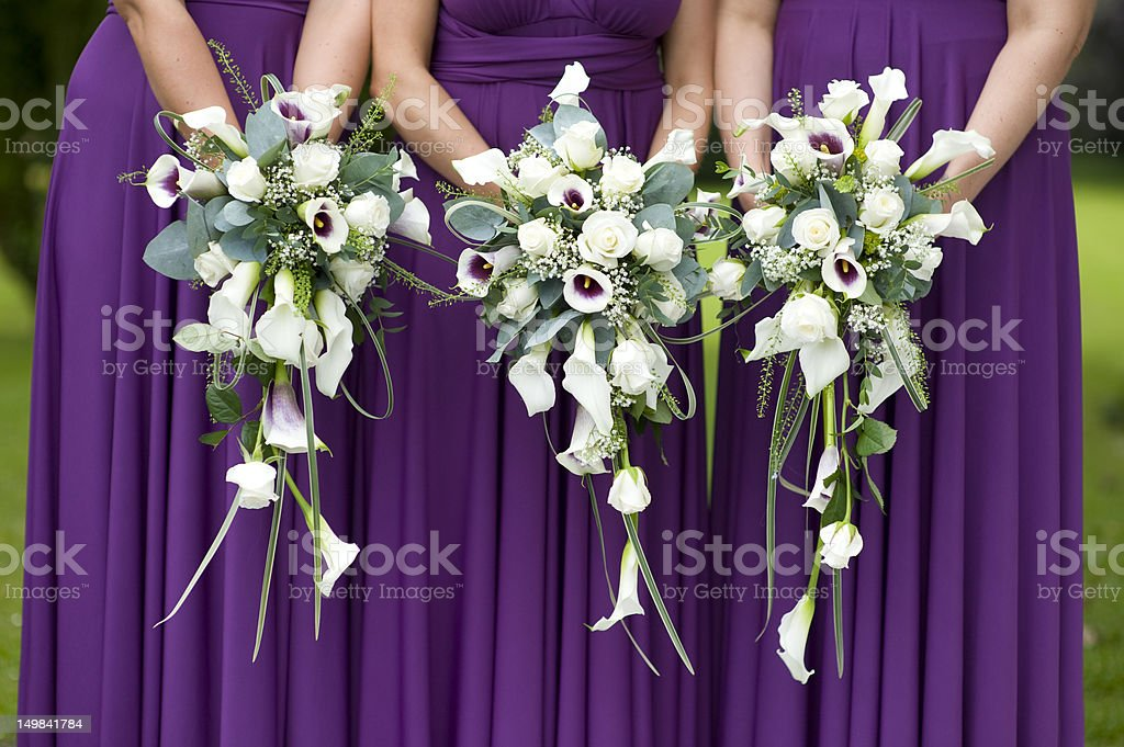 three bridesmaids holding wedding bouquets stock photo