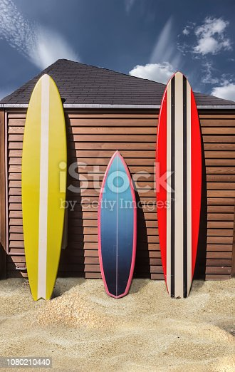 The concept of relaxing on the water. Three bright surfboards stand on the sand of the beach under the blue sky near the sea.