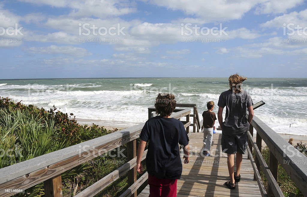 Three brothers walking towards the ocean, Cape Canaveral  National Seashore stock photo