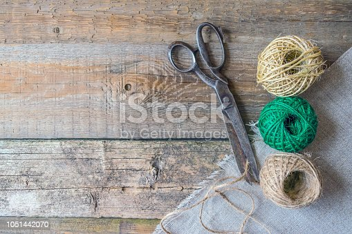 Three brown and green thread ball with antique vintage scissors on textured old wooden boards. Rustic, wabi sabi needlework, hobby, sewing and tailoring