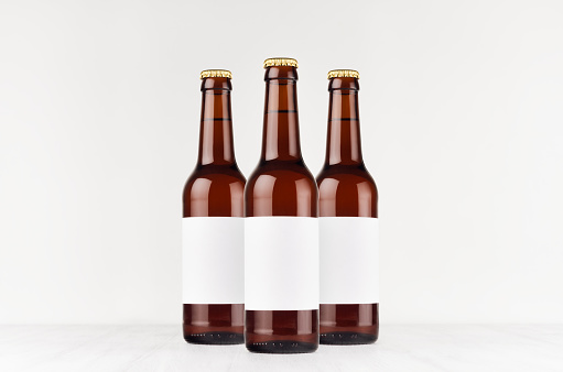 Three brown longneck beer bottles 330ml with blank white label on white wooden board, mock up.