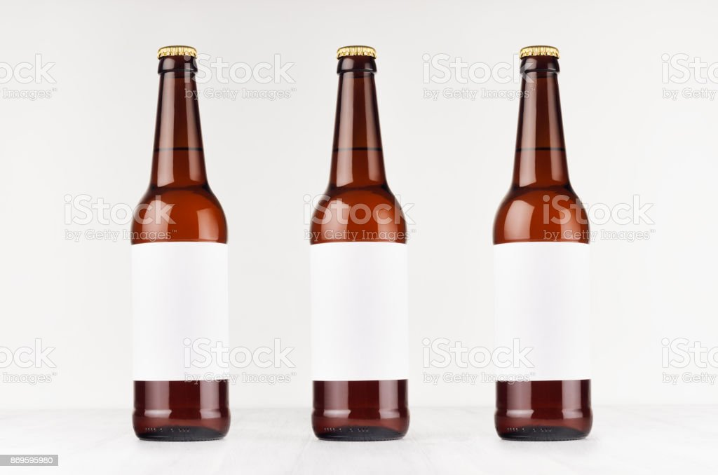 Three brown longneck beer bottles 500ml with blank white label on white wooden board, mock up. stock photo