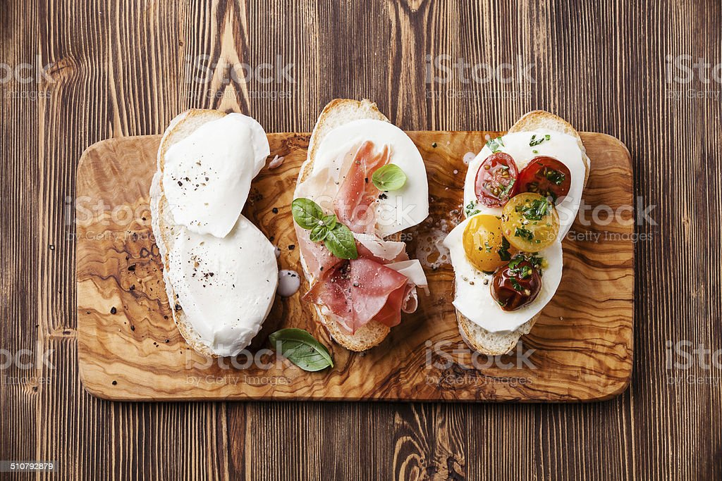 Three bruschettas with mozzarella, ham and tomatoes stock photo
