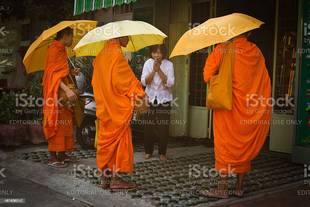Three Buddhist monks bless a lady in Phnom Phen, Cambod stock photo