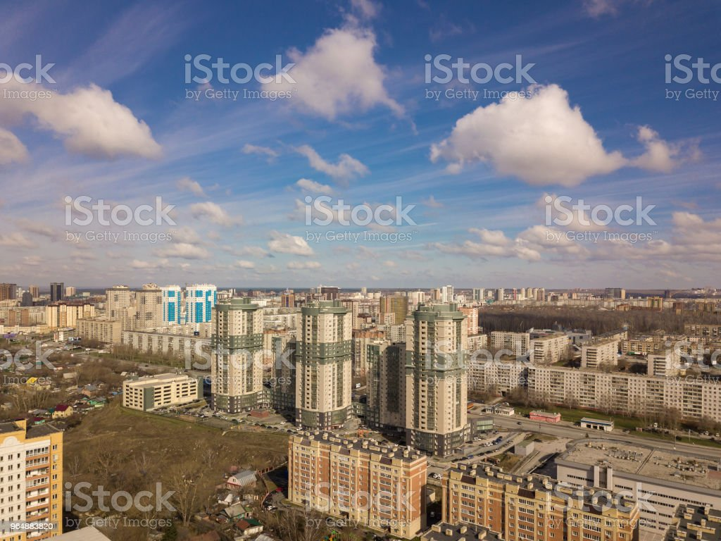 Three buildings in the city colored in green and grey and blue sky with clouds. Different buildings from small to large royalty-free stock photo