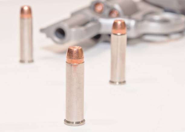 Three bullets in front of a loaded revolver stock photo
