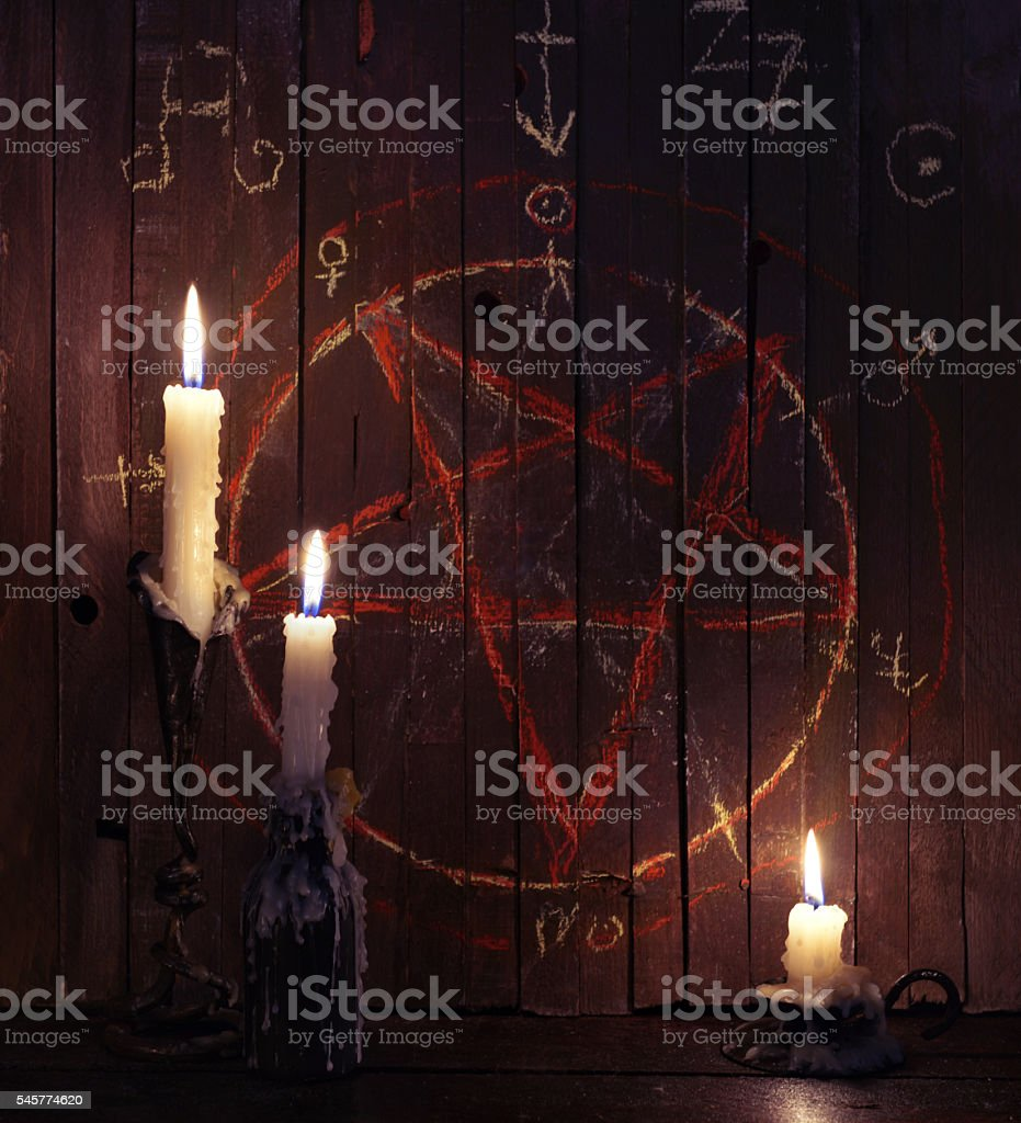 Three burning candles and wooden planks with pentagram stock photo