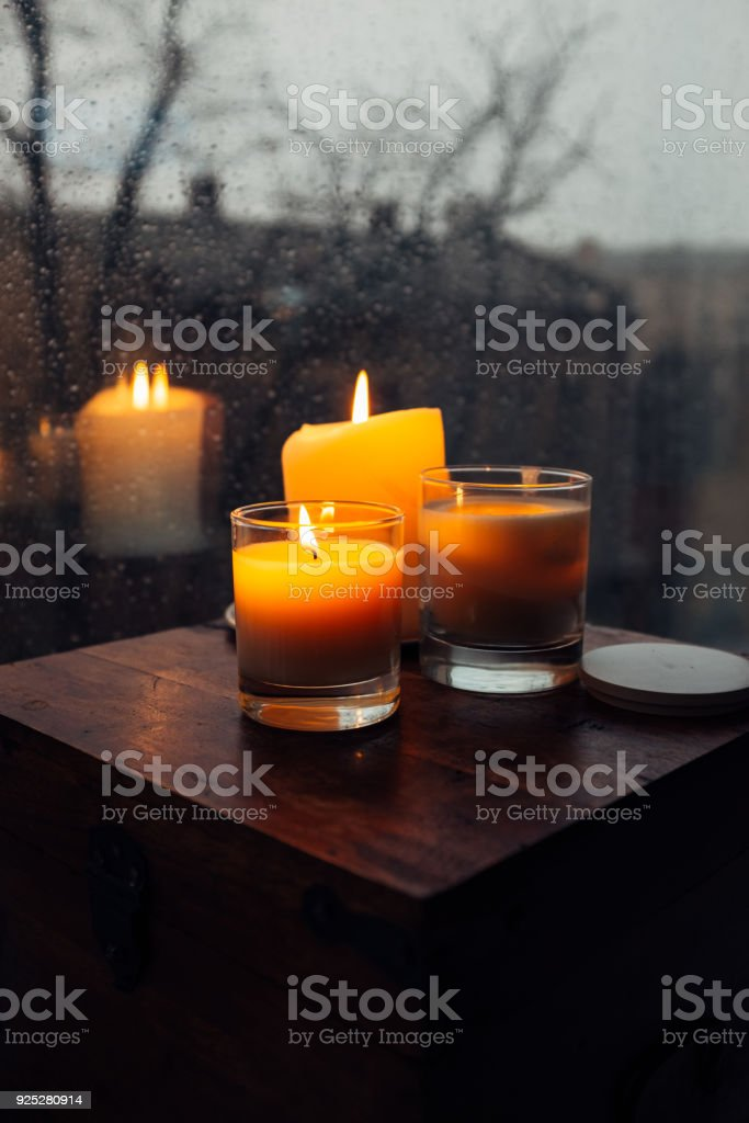 Three burning candles on table, cozy rainy day an home stock photo