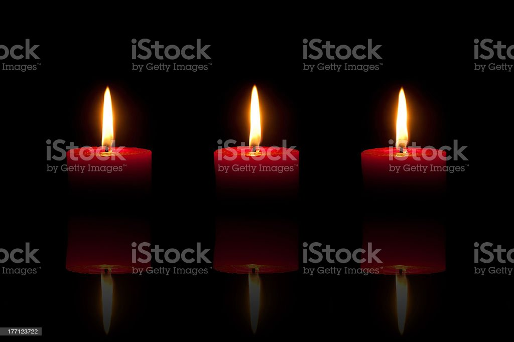 Three burning red candles in front of black background royalty-free stock photo