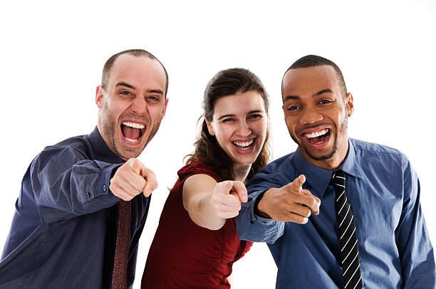 Three business adults smiling and pointing at the camera stock photo