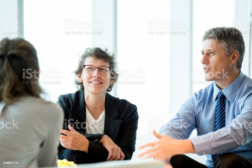 Three Business Colleagues Meeting in Lounge stock photo