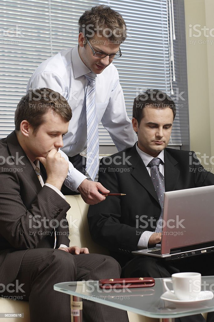 Three business men working together on latop in the office royalty-free stock photo