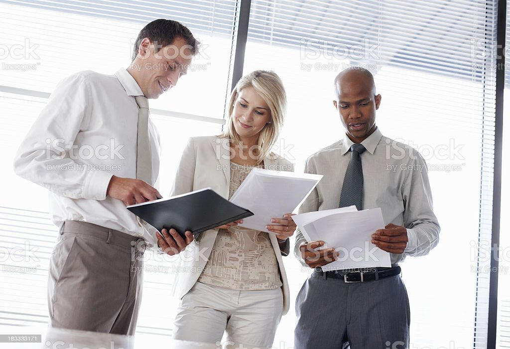 Three business partners going through their documents royalty-free stock photo