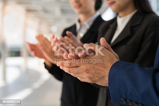 istock Three business people clap their hands to congratulate the signing of an agreement or contract between their firms, companies, enterprises. success, dealing, greeting and partner concept. 843888228